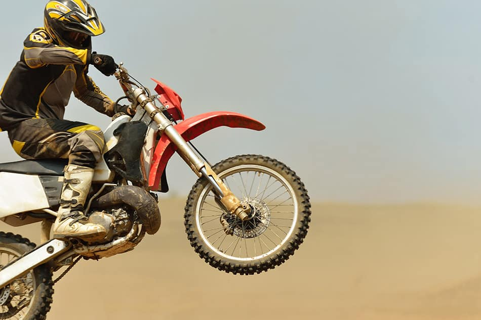 Dirt bike rider doing a wheelie at the sand dunes.