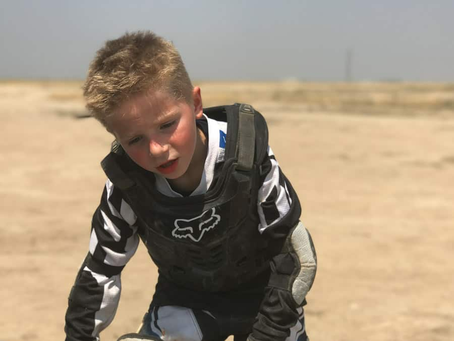 Kid really thirsty and ready for a break after dirt biking.