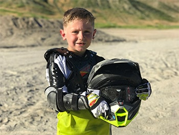 8-year-old boy holding a dirt bike helmet and wearing protective gear.